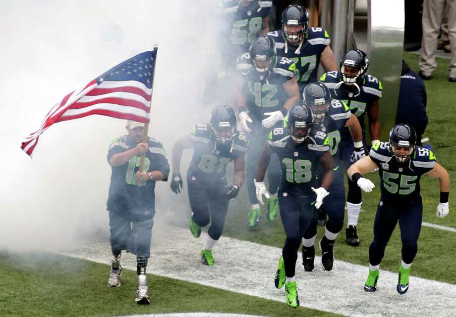 "U.S. Army Sgt. Erin M. Schaefer, (Ret.) a double amputee who received a Purple Heart for injuries suffered in Afghanistan in 2010 during his fourth tour of duty, helps lead the Seattle Seahawks onto the field for an NFL football game against the New York Jets, Sunday, Nov. 11, 2012, in Seattle. Schaefer was part of the NFL's ""Salute to Service"" tribute to veterans. Photo: AP"