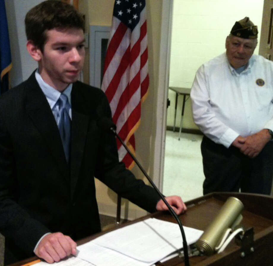 Staples High School senior Ian Teran delivers the Veterans Day address Sunday during a Town Hall ceremony as William Vornkahl, master of ceremonies, looks on. Westport CT 11/11/12 Photo: Andrew Brophy / Westport News contributed