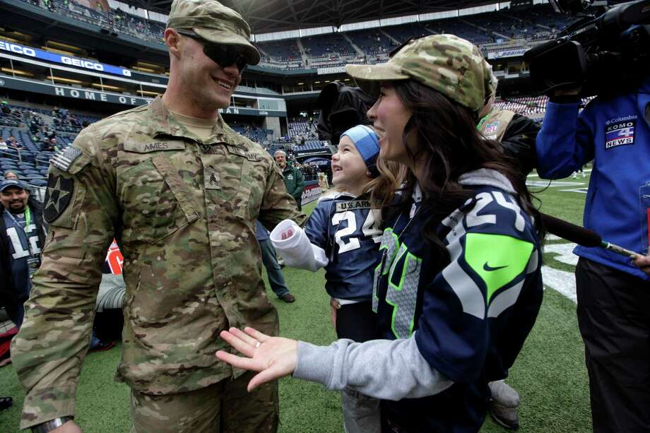United States Army Sgt. Zach Ames, left, who had been on a one-year deployment to Afghanistan, surprises his wife, Bri Ames, right, and their daughter Emersyn with a reunion on the field before an NFL football game between the New York Jets and the Seattle Seahawks on Veterans Day, Sunday, Nov. 11, 2012, in Seattle. Photo: AP