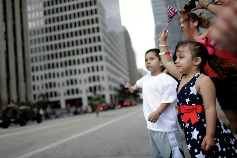 3-year-old Nevaeh Shelton, right, and brother, 4-year-old Wesley Shelton, wave US flags in support along the parade route, Sunday, November 11, 2012 during the 2012 Veteran's Day Parade in Downtown Houston, Texas. (TODD SPOTH FOR THE CHRONICLE) Photo: TODD SPOTH, TODD SPOTH / PHOTOGRAPHER / © TODD SPOTH, 2012