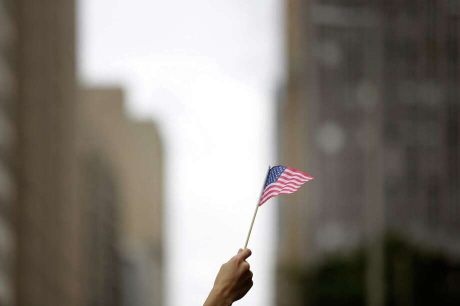 Claudia Ramirez holds up a US flag in support, Sunday, November 11, 2012 during the 2012 Veteran's Day Parade in Downtown Houston, Texas. (TODD SPOTH FOR THE CHRONICLE) Photo: TODD SPOTH, TODD SPOTH / PHOTOGRAPHER / © TODD SPOTH, 2012