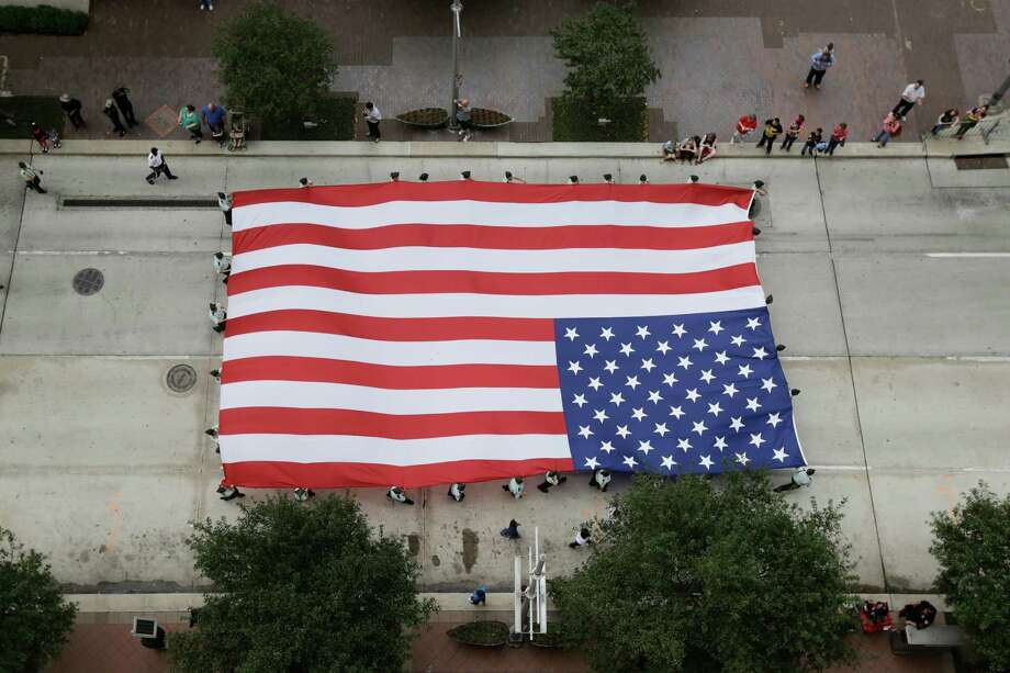 A giant US flag is seen being carried down Lamar Street, Sunday, November 11, 2012 during the 2012 Veteran's Day Parade in Downtown Houston, Texas. (TODD SPOTH FOR THE CHRONICLE) Photo: TODD SPOTH, TODD SPOTH / PHOTOGRAPHER / © TODD SPOTH, 2012
