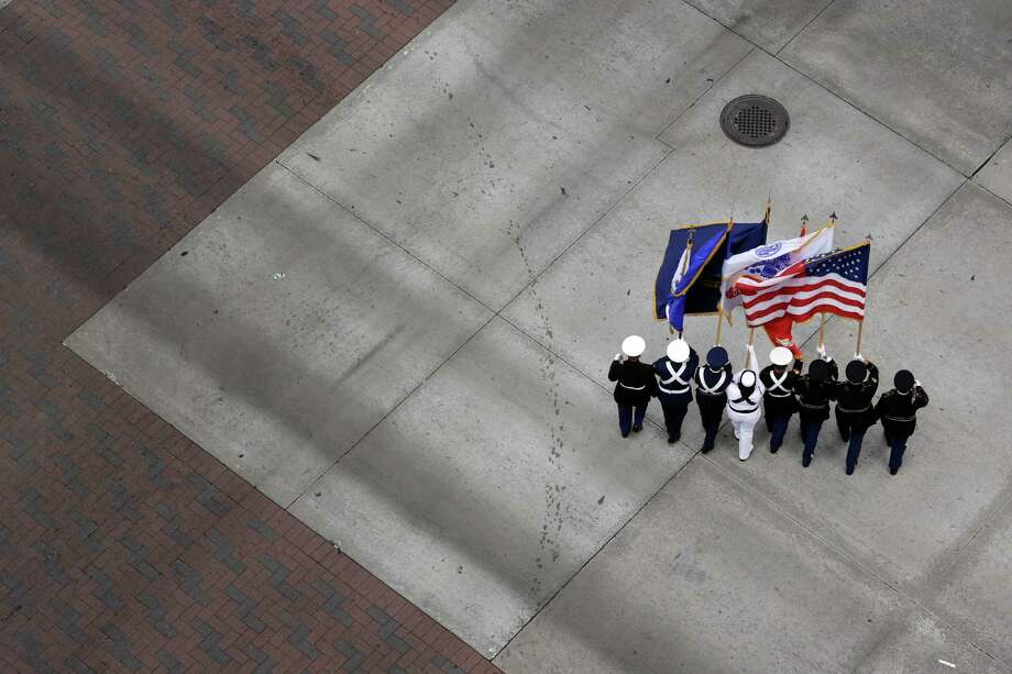 The honor guard carrying flags representing all branches of the armed services, turns onto Smith Street from Lamar Street, Sunday, November 11, 2012 during the 2012 Veteran's Day Parade in Downtown Houston, Texas. (TODD SPOTH FOR THE CHRONICLE) Photo: TODD SPOTH, TODD SPOTH / PHOTOGRAPHER / © TODD SPOTH, 2012