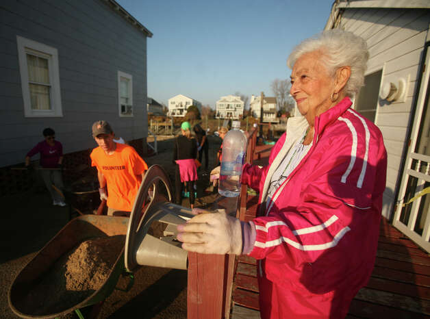 Virginia Moore smiles as she watches a crew of volunteers clear sand from around her house at 2262 Fairfield Beach Road in Fairfield on Sunday, November 11, 2012. Moore said her family built the house in 1945. Photo: Brian A. Pounds / Connecticut Post