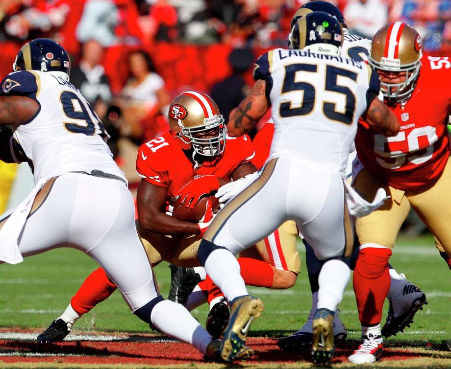 Running back Frank Gore (21) runs through St. Louis Rams linebacker James Laurinaitis (55) and St. Louis Rams defensive tackle Trevor Laws (99)  during the first quarter of the San Francisco 49ers game against the St. Louis Rams at Candlestick Park in San Francisco, Calif., on Sunday November 11, 2012. Photo: Carlos Avila Gonzalez, The Chronicle / ONLINE_YES