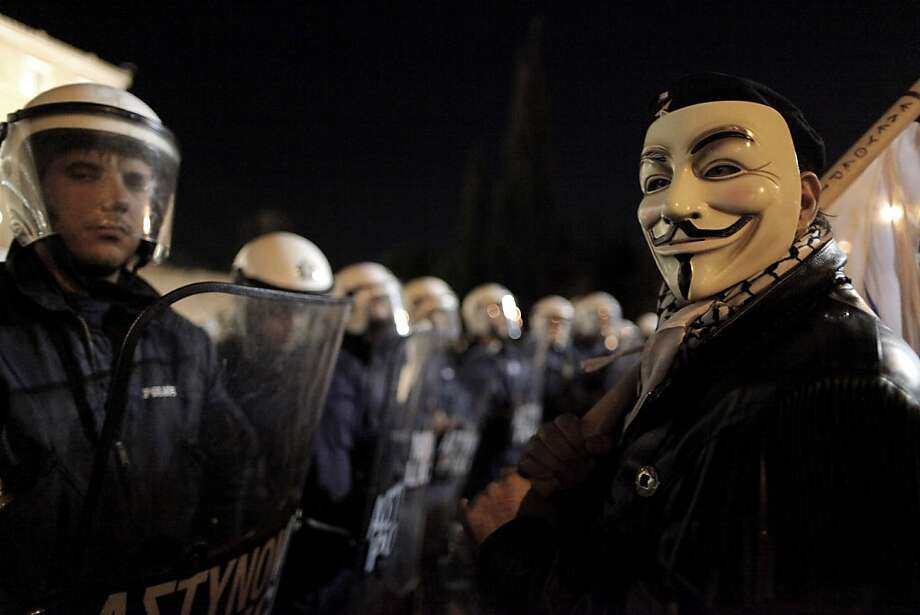 A demonstrator wearing an antiestablishment Guy Fawkes mask stands next to riot police guarding the Greek Parliament during an antiausterity rally in central Athens on Sunday. Photo: Petros Giannakouris, Associated Press