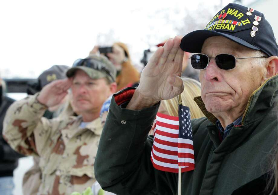 World War II combat veteran Ben Kauffman, age 86, carries an American flag as he listens to a speaker during a Veterans Day ceremony in the small town of Loveland, Colo., Sunday Nov. 11, 2012. Kauffman, who fought in the Battle of Okinawa in 1945 with the U.S. Army's 17th Infantry Regiment, also served in Korea. (AP Photo/Brennan Linsley) Photo: Brennan Linsley, Associated Press / AP
