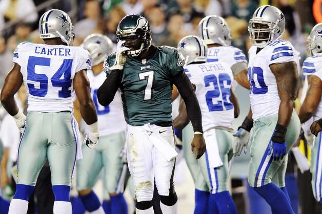 Philadelphia Eagles quarterback Michael Vick (7) adjusts his helmet after being tackled in the first half of an NFL football game against the Dallas Cowboys, Sunday, Nov. 11, 2012, in Philadelphia. (AP Photo/Michael Perez) (Associated Press)