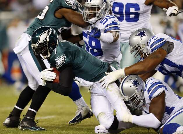 Philadelphia Eagles quarterback Michael Vick, left, is tackled by Dallas Cowboys inside linebacker Ernie Sims, defensive end Jason Hatcher and outside linebacker DeMarcus Ware in the first half of an NFL football game, Sunday, Nov. 11, 2012, in Philadelphia. Julio Cortez/Associated Press