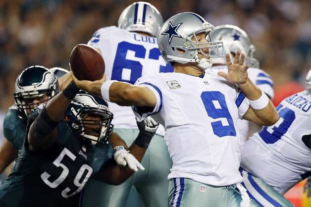 Dallas Cowboys quarterback Tony Romo, right, passes under pressure from Philadelphia Eagles middle linebacker DeMeco Ryans in the first half of an NFL football game, Sunday, Nov. 11, 2012, in Philadelphia. (AP Photo/Julio Cortez) (Associated Press)