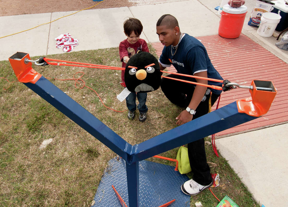 With the help of Jamal shelvin (right), 5 year old Kevin Dixon gets ready to launch an Angry Bird during the Monster Mash Pumpkin Smash at UTSA Sunday afternoon.