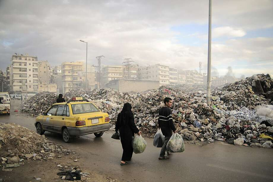 Syrians carry their rubbish to a heap of garbage at a roundabout in Aleppo. Due to heavy fighting and shelling, the garbage collection system collapsed weeks ago, forcing people to improvise trash disposal. Photo: Mónica G. Prieto, Associated Press