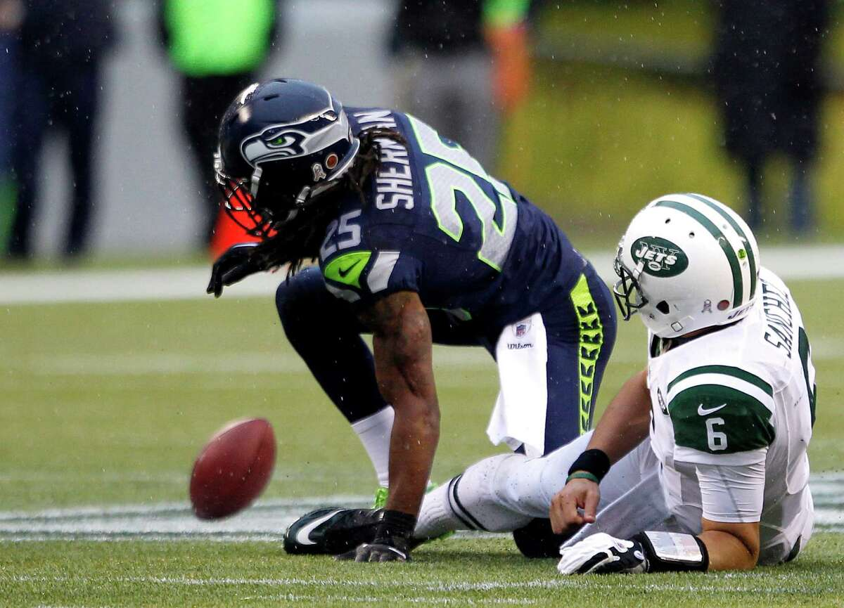 New York Jets quarterback Mark Sanchez, right, looks at his fumble, which was recovered by the Seattle Seahawks, after he was tackled by Seahawks' Richard Sherman, during the second half of an NFL football game, Sunday, Nov. 11, 2012, in Seattle.