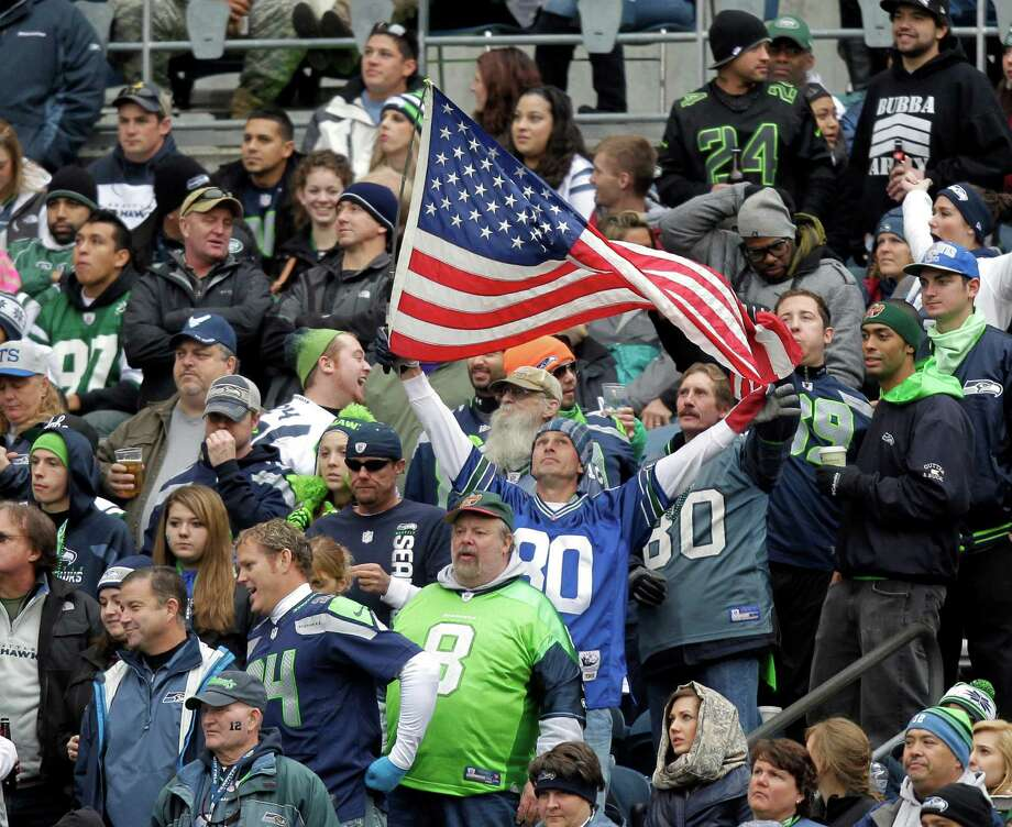"A fan in the stands displays the U.S. flag during an NFL football game between the New York Jets and the Seattle Seahawks, Sunday, Nov. 11, 2012, in Seattle. The NFL focused the game on ""Salute to Service"" in tribute to members of the military and veterans. Photo: AP"