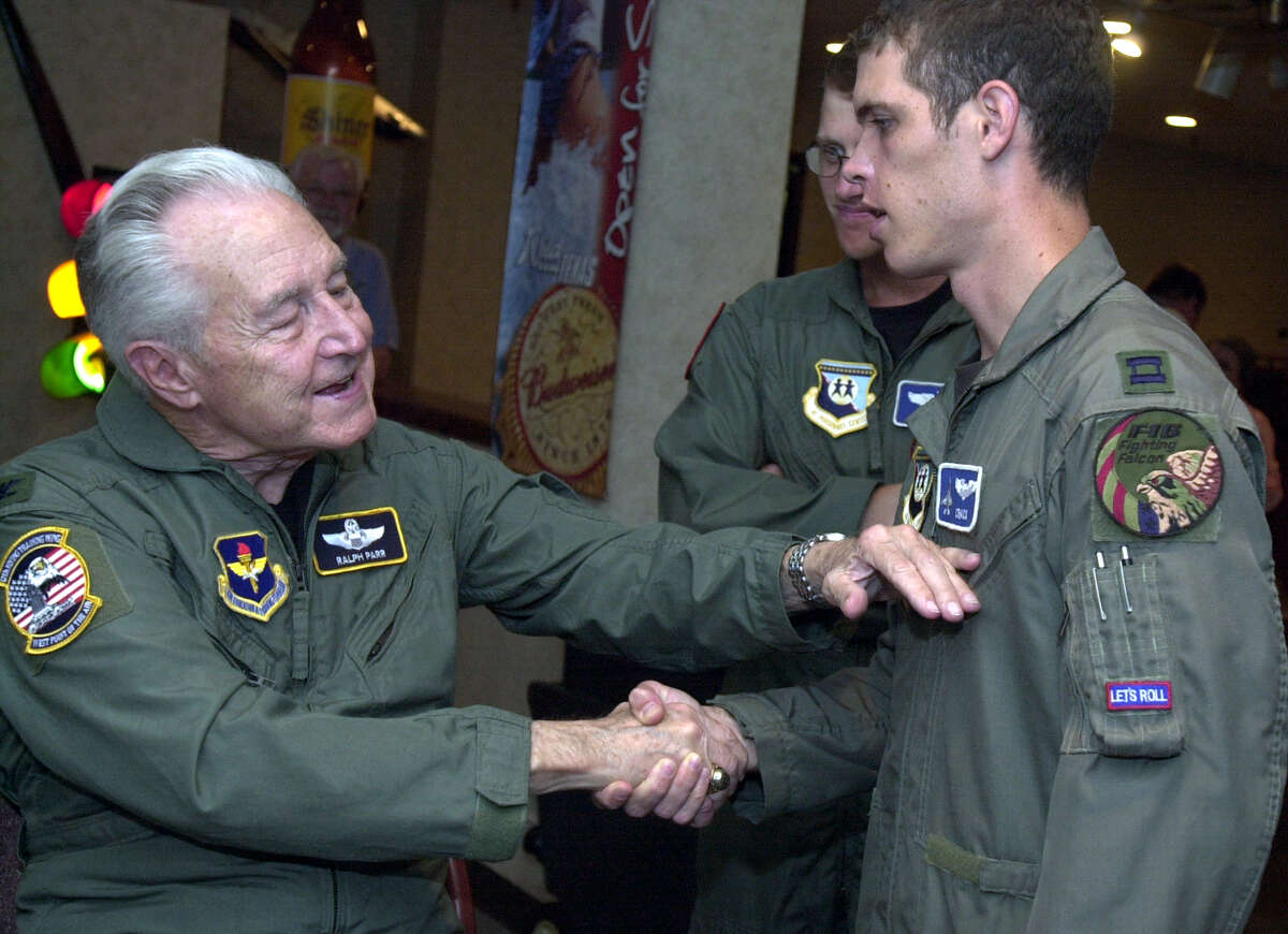 Ralph Parr (left)is a Korean War ace. He is seen Friday, July 25, 2003, at the Officers Club at Randolph Air Force Base during a party thrown in his honor. He says good-bye to Capt. Doyle Pompa (right) and Major Geoff Laing (rear), who both thanked him for his example. (KAREN L. SHAW/STAFF)