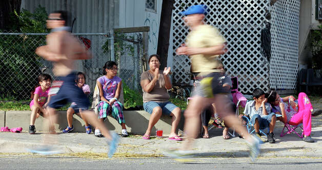 Spectators watch marathon runners pass along Mission Road during the Rock 'n' Roll San Antonio Marathon and 1/2 Marathon Sunday Nov. 11, 2012. Photo: Edward A. Ornelas, San Antonio Express-News / © 2012 San Antonio Express-News