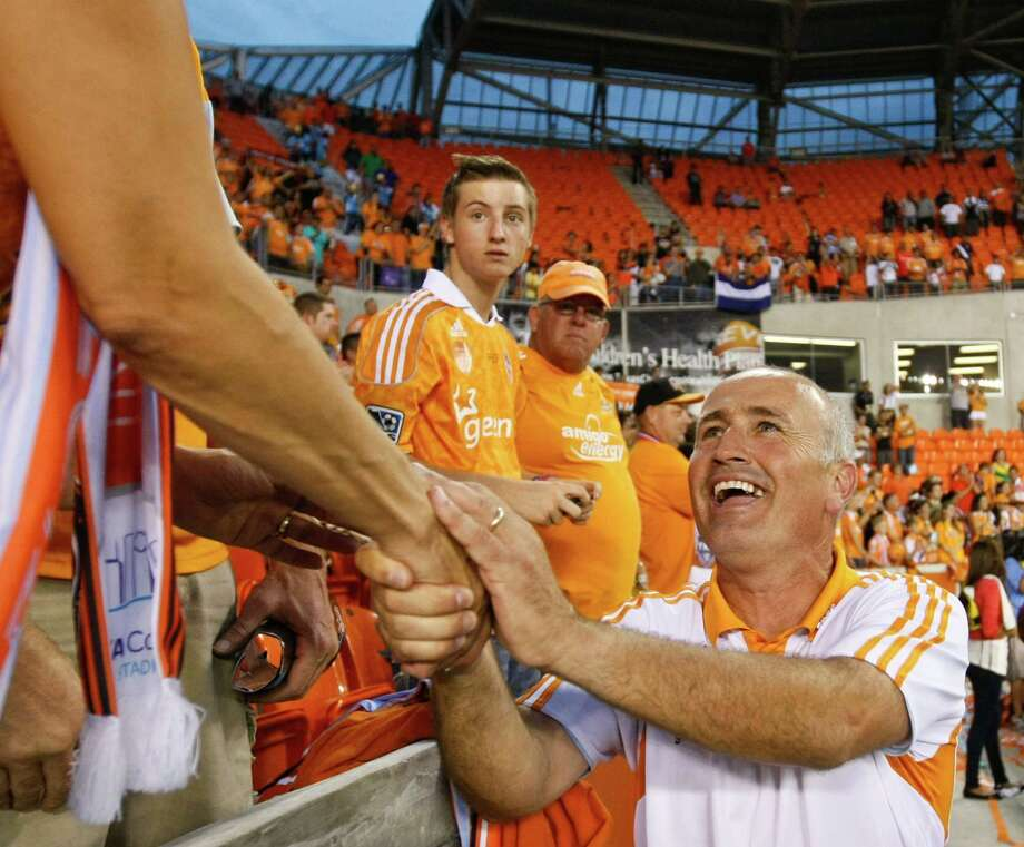 Houston Dynamo head coach Dominic Kinnear shakes hands with fans after winning a MLS playoff game against D.C. United, Sunday, Nov. 11, 2012,  in BBVA Compass Stadium in Houston. Photo: Nick De La Torre, Houston Chronicle / © 2012  Houston Chronicle