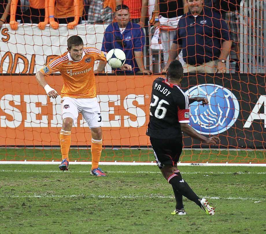 Bobby Boswell #32 of the Houston Dynamo saves a goal by blocking D.C. United forward Lionard Pajoy #26 shot half of a MLS playoff game , Sunday, Nov. 11, 2012,  in BBVA Compass Stadium in Houston. Photo: Nick De La Torre, Houston Chronicle / © 2012  Houston Chronicle