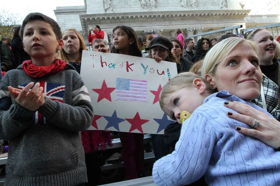 Jamie Trachtenberg, of Chicago, Illinois, right, holds her son Evan Trachtenberg, 2, as they and others watch the Veterans Day Parade makes it's way up New York's Fifth Avenue Sunday Nov. 11, 2012.   (AP Photo/Tina Fineberg) Photo: Tina Fineberg