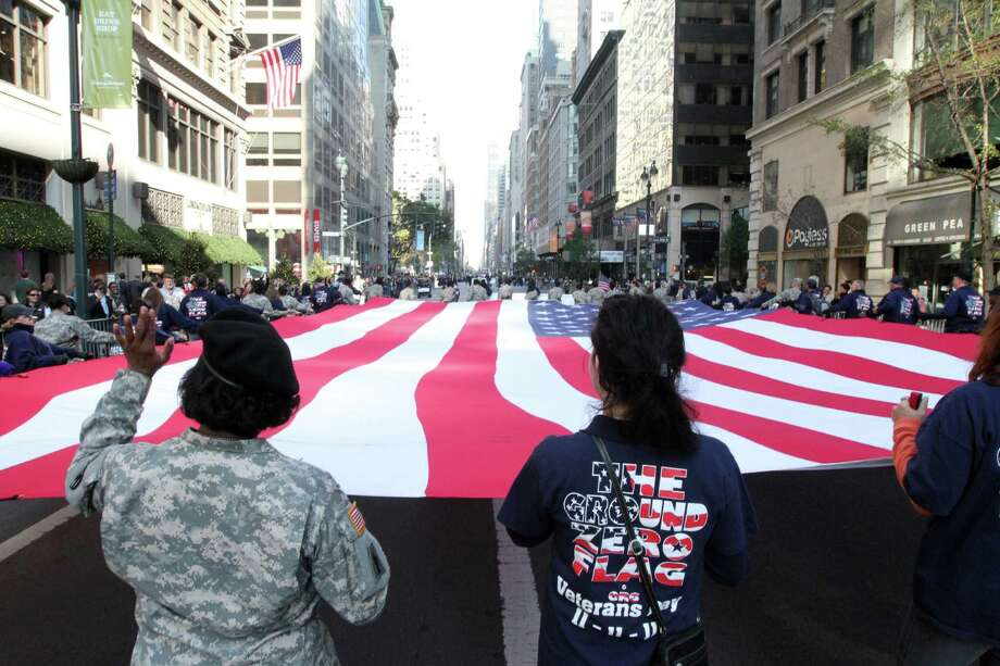 The American flag is carried up New York's Fifth Avenue during the Veterans Day Parade Sunday Nov. 11, 2012. (AP Photo/Tina Fineberg) Photo: Tina Fineberg