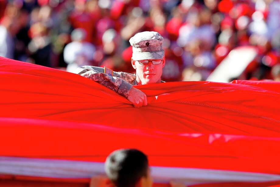 In honor of Veterans Day, members of the military and their families stretched out the flag during the national Anthem. The San Francisco 49ers play the St. Louis Rams at Candlestick Park in San Francisco, Calif., on Sunday November 11, 2012. Photo: Brant Ward, The Chronicle / ONLINE_YES