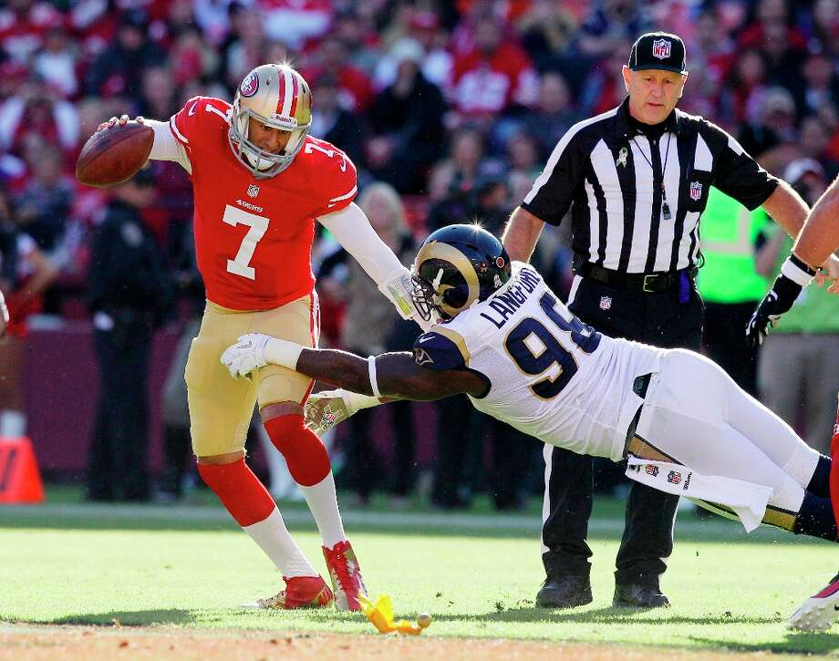 San Francisco 49ers quarterback Colin Kaepernick, left, tries to break away from St. Louis Rams defensive tackle Kendall Langford, right, during the second quarter of an NFL football game in San Francisco, Sunday, Nov. 11, 2012 Photo: Jeff Chiu, Associated Press / AP