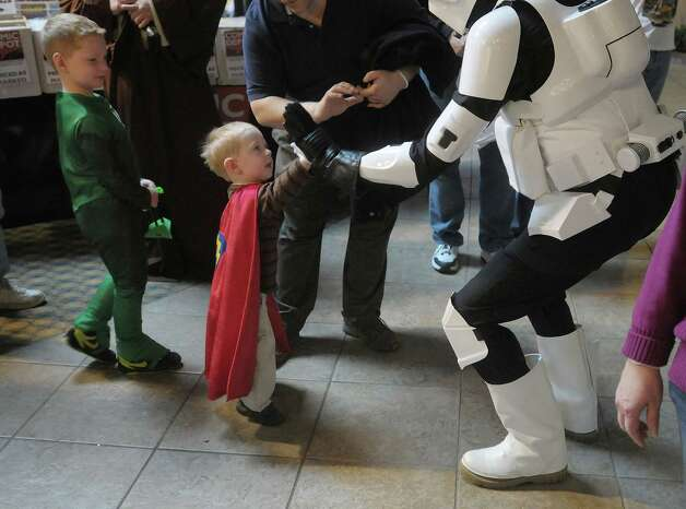 Jack Lurie, 2, from Glenmont gives a high five to a man dressed as a Star Wars character,  as his older brother, Paul Lurie, left, 6, dresses as the Green Lantern looks on during the 5th annual Albany Comic Con on Sunday, Nov. 11, 2012 at the Holiday Inn in Albany, NY.  (Paul Buckowski / Times Union) Photo: Paul Buckowski