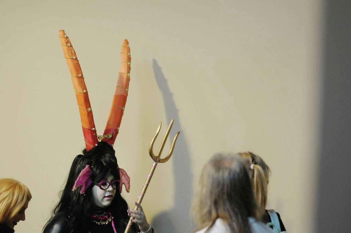 Kayla Noonan from Claverack, NY dresses as web comic character Condesce from Homestuck, talks with other attendees during the 5th annual Albany Comic Con on Sunday, Nov. 11, 2012 at the Holiday Inn in Albany, NY. Noonan made all the parts of her attire, carving the horns out of styrofoam and using six different wigs to make the hair piece. (Paul Buckowski / Times Union)