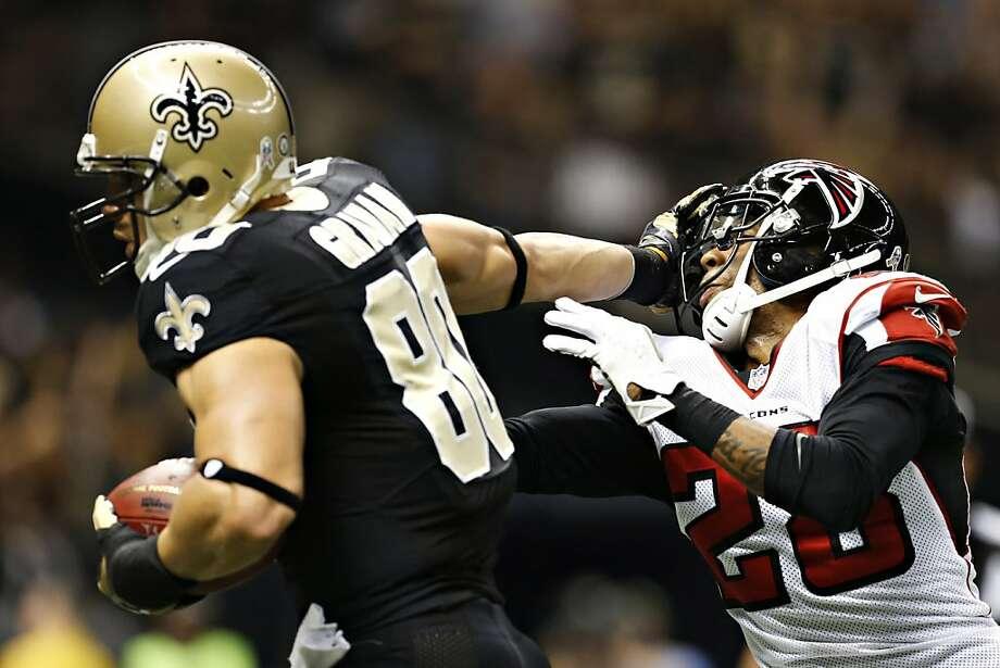 Saints tight end Jimmy Graham stiff-arms Atlanta's Thomas DeCoud en route to a touchdown. Photo: Wesley Hitt, Getty Images
