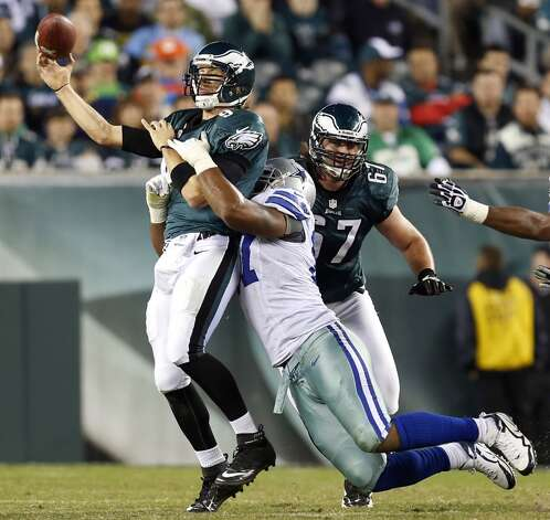 Philadelphia Eagles quarterback Nick Foles, left, is hit by Dallas Cowboys' Jason Hatcher as he throws in the second half of an NFL football game, Sunday, Nov. 11, 2012, in Philadelphia. (AP Photo/Julio Cortez) (Associated Press)