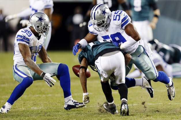Dallas Cowboys' Brandon Carr, left, intercepts a pass intended for Philadelphia Eagles DeSean Jackson as Jackson is hit by Ernie Sims in the second half of an NFL football game, Sunday, Nov. 11, 2012, in Philadelphia. Carr returned the interception 47 yards for a touchdown. Julio Cortez/Associated Press