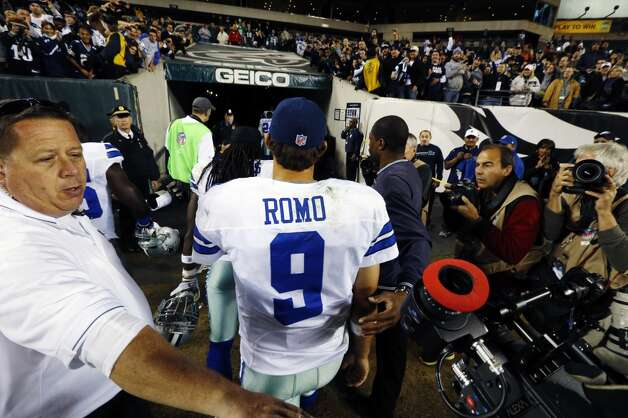 Dallas Cowboys quarterback Tony Romo is escorted off the field after an NFL football game against the Philadelphia Eagles, Sunday, Nov. 11, 2012, in Philadelphia. Dallas won 38-23. (AP Photo/Julio Cortez) (Associated Press)
