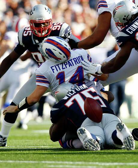 Bills QB Ryan Fitzpatrick loses the ball on a sack by Vince Wilfork (75) and Jermaine Cunningham. Photo: Jared Wickerham, Staff / 2012 Getty Images