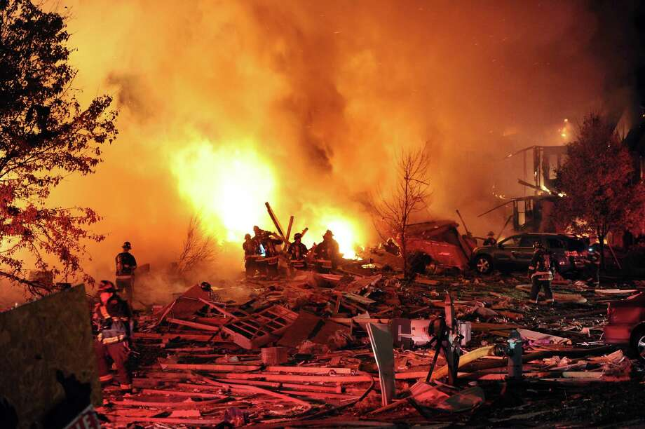 Authorities say a loud explosion has leveled a home in Indianapolis and set four others ablaze in a neighborhood, causing several injuries. Capt. Rita Burris with the Indiana Fire Department told The Associated Press that firefighters are still working to put out the flames after the explosion around 11 p.m. Saturday Nov. 10, 2012. (AP Photo/The Indianapolis Star, Matt Kryger) Photo: Matt Kryger, MBR / The Indianapolis Star