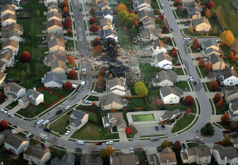 This aerial photo shows the two homes that were leveled and the numerous neighboring homes that were damaged from a massive explosion that sparked a huge fire and killed two people, Sunday, Nov. 11, 2012, in Indianapolis.  Nearly three dozen homes were damaged or destroyed, and seven people were taken to a hospital with injuries, authorities said Sunday. The powerful nighttime blast shattered windows, crumpled walls and could be felt at least three miles away. (AP Photo/The Indianapolis Star, Matt Kryger)  NO SALES Photo: Matt Kryger, MBO / Indianapolis Star