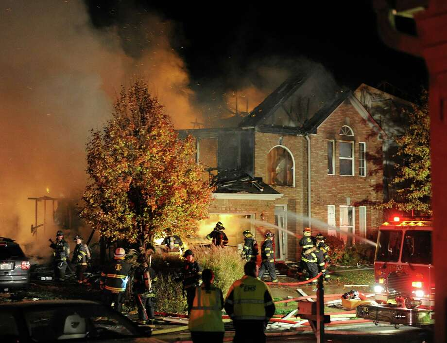 Firefighters work the scene where an explosion has killed two people and damaged more than a dozen homes in the Richmond Hill subdivision, late Saturday, Nov. 10, 2012, in Indianapolis. (AP Photo/The Indianapolis Star, Matt Kryger) Photo: Matt Kryger, MBO / The Indianapolis Star
