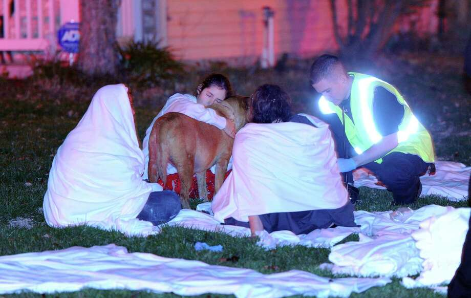 Paramedics attend to the some of the people hurt from the multiple home explosions on the southside of Indianapolis Saturday Nov. 10, 2012. Authorities say a loud explosion has leveled a home in Indianapolis and set four others ablaze in a neighborhood, causing several injuries. Capt. Rita Burris with the Indiana Fire Department told The Associated Press that firefighters are still working to put out the flames after the explosion around 11 p.m. Saturday. (AP Photo/The Indianapolis Star, Matt Kryger) Photo: Matt Kryger, MBR / The Indianapolis Star