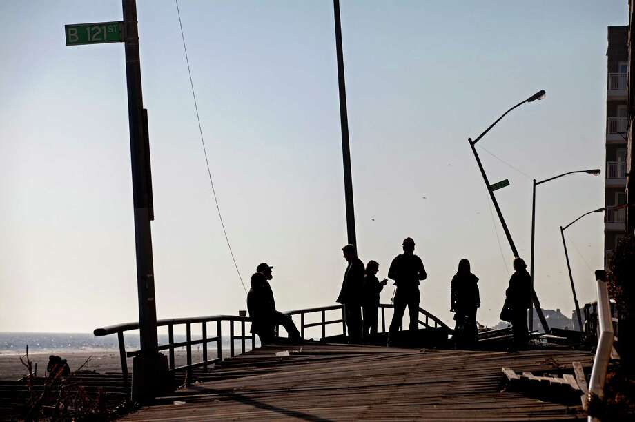 People gather on the buckled boardwalk of the Rockaway Park neighborhood of the borough of Queens, New York, Sunday, Nov. 11, 2012, in the wake of Superstorm Sandy. (AP Photo/Craig Ruttle) Photo: Craig Ruttle