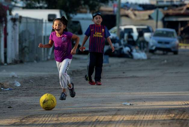 Nicoll Cortez, 6, gleefully chases a soccer ball as she plays with her brother Anthony Lopez, 7, on their sand and debris covered street in the Rockaway Park neighborhood of the borough of Queens, New York, Sunday, Nov.11, 2012, in the wake of Superstorm Sandy. (AP Photo/Craig Ruttle) Photo: Craig Ruttle