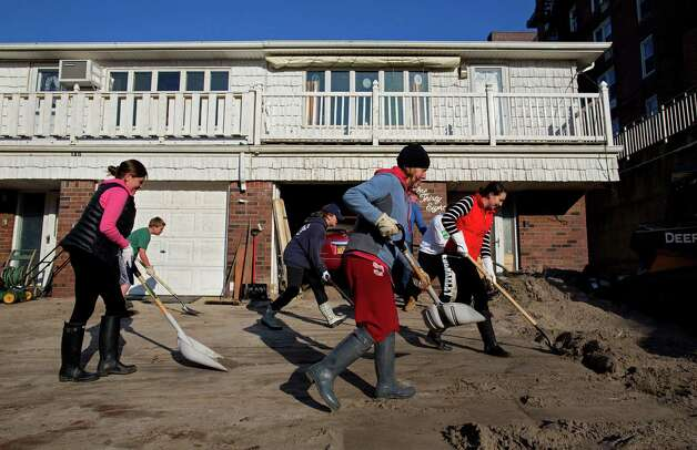 Neighbors volunteering to help another neighbor in need move deep sand from the house on Beach 121 Street in the Rockaway Park neighborhood of the borough of Queens, New York, Sunday, Nov. 11, 2012, in the wake of Superstorm Sandy. (AP Photo/Craig Ruttle) Photo: Craig Ruttle