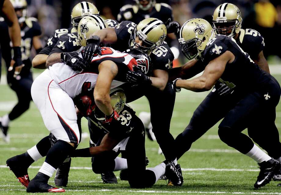 Atlanta Falcons running back Michael Turner (33) is stopped by New Orleans Saints middle linebacker Curtis Lofton (50), cornerback Jabari Greer (33), defensive end Cameron Jordan (94) and outside linebacker Jonathan Vilma (51) in the second half of an NFL football game at Mercedes-Benz Superdome in New Orleans, Sunday, Nov. 11, 2012. (AP Photo/Bill Haber) Photo: Bill Haber