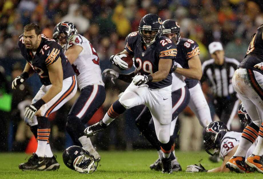 Chicago Bears running back Michael Bush (29) rushes against the Houston Texans as teammate tackle Gabe Carimi (72) loses his helmet in the first half an NFL football game in Chicago, Sunday, Nov. 11, 2012. (AP Photo/Nam Y. Huh) Photo: Nam Y. Huh, Associated Press / AP