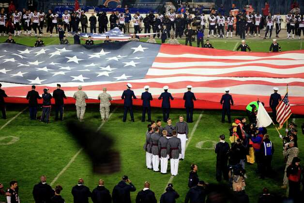 "Military personnel hold a giant flag as the West Point ""Knight Caps"" Glee Club, foreground, sings the national anthem as part of the NFL's Salute to Service campaign on Veterans Day before an NFL football game between the Chicago Bears and Houston Texans, Sunday, Nov. 11, 2012, in Chicago. (AP Photo/Kiichiro Sato) Photo: Kiichiro Sato, Associated Press / AP"
