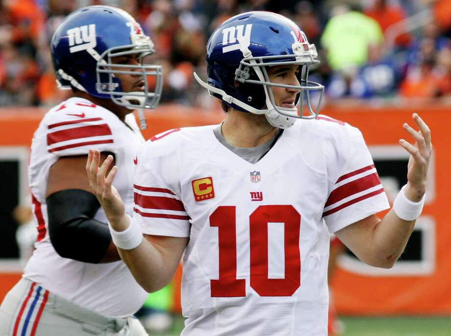 New York Giants quarterback Eli Manning (10) holds up his hands after having a pass tipped for an interception in the second half of an NFL football game against the Cincinnati Bengals, Sunday, Nov. 11, 2012, in Cincinnati. (AP Photo/Tom Uhlman) Photo: Tom Uhlman