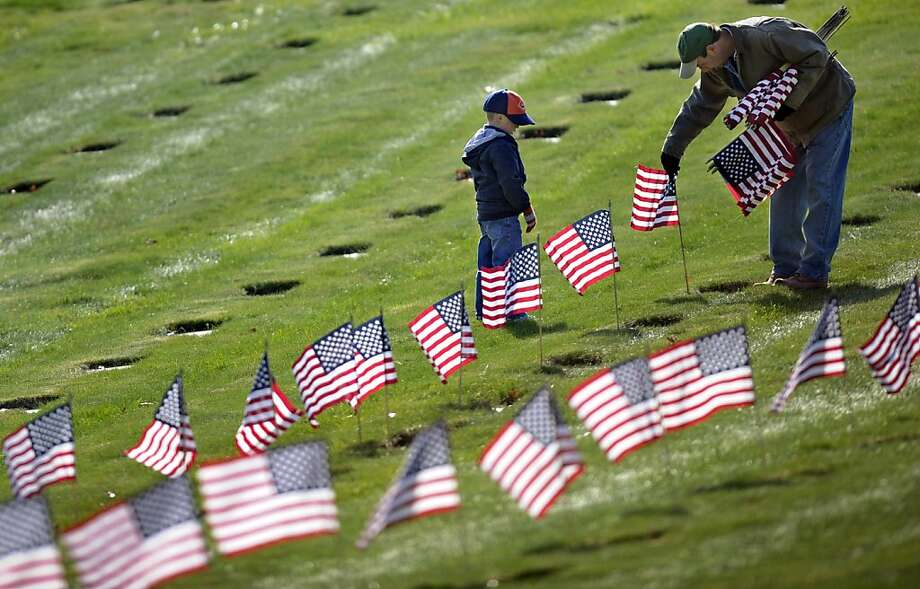 Joseph Manning, right, of Raynham, Mass., and his son Joey, 6, a Cub Scout, place U.S. flags at the graves of deceased veterans at the National Cemetery in Bourne, Mass., Saturday, Nov. 10, 2012.  Thousands of flags were placed in the cemetery in advance of Veterans Day. (AP Photo/Gretchen Ertl) Photo: Gretchen Ertl, Associated Press