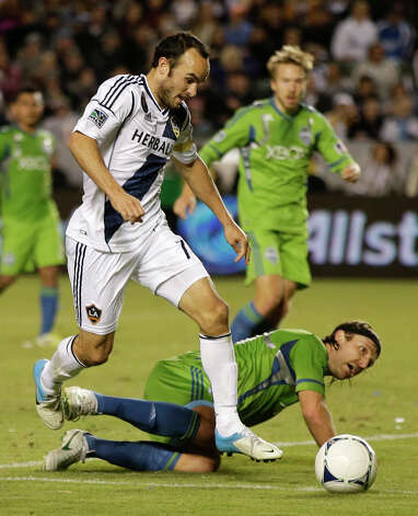 Los Angeles Galaxy's Landon Donovan, left, kicks the ball past Seattle Sounders' Steve Zakuani setting up their goal during the first half of an MLS Western Conference finals soccer game in Carson, Calif., Sunday, Nov. 11, 2012. Photo: AP