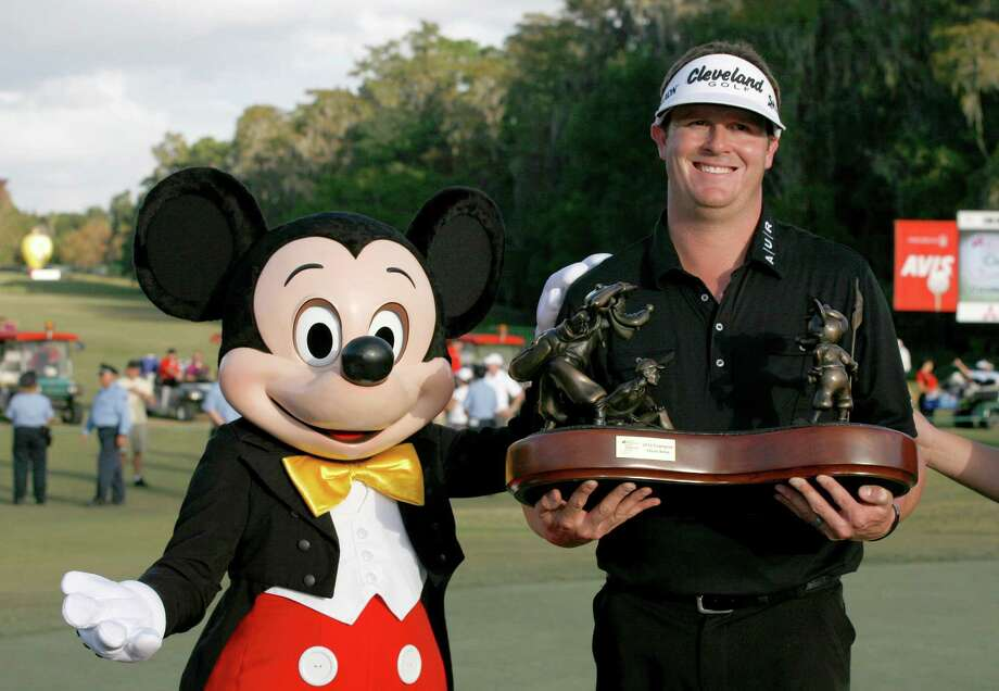 """Charlie Beljan, right, and """"Mickey Mouse"""" hold up the trophy on the 18th green following the final round of the Children's Miracle Network Hospitals golf tournament in Lake Buena Vista, Fla., Sunday, Nov. 11, 2012. (AP Photo/Reinhold Matay) Photo: Reinhold Matay, FRE / FR156687 AP"""
