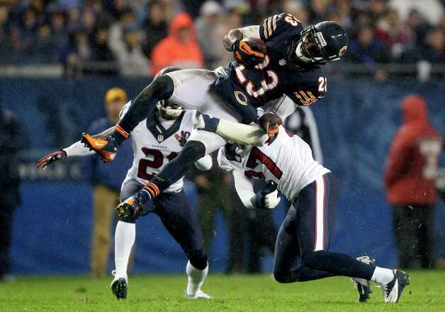 Chicago Bears wide receiver Devin Hester (23) tackled by Houston Texans defensive back Quintin Demps (27) in the first half an NFL football game in Chicago, Sunday, Nov. 11, 2012. Texans defensive back Brice McCain (21) comes in from behind. (AP Photo/Nam Y. Huh) Photo: Nam Y. Huh, Associated Press / AP