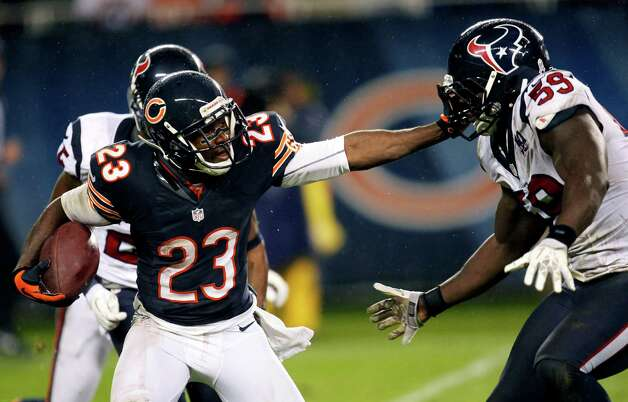 Chicago Bears' Devin Hester (23) stiff-arms Houston Texans' Whitney Mercilus (59) during a punt return during the second half, Nov. 11, 2012, in Chicago. (AP Photo/Charles Rex Arbogast) Photo: Charles Rex Arbogast, Associated Press / AP