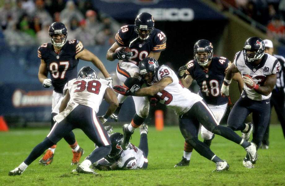 Chicago Bears running back Michael Bush (29) leaps over Houston Texans safeties Danieal Manning (38) and Glover Quin (29) as they try to tackle him during the second half of an NFL football game, Sunday, Nov. 11, 2012,in Chicago. (AP Photo/Nam Y. Huh) Photo: Nam Y. Huh, Associated Press / AP